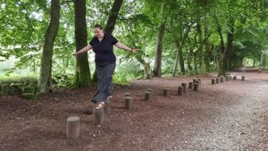 Ruth hops across balancing logs in the Darwin Forest.