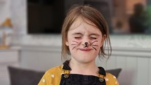 A girl with felt-tip whiskers drawn on to look like a cat.