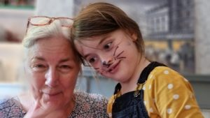 A woman and a girl; the girl is face-painted as a cat, the woman has bit of the face paint rubbed off onto her.