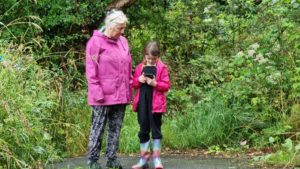 A woman and a girl outdoors looking at their mobile devices.