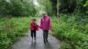 A woman and a girl on a cycleway, holding hands, between trees and weeds.