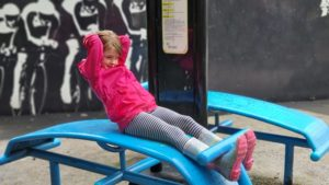 A girl does sit-ups in an outdoor gym.