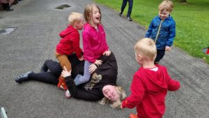 Becky lies on the floor, surrounded by/covered in children.