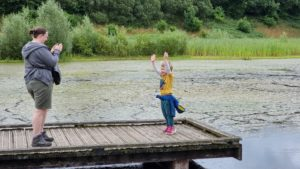 Ruth photographs her 4-year-old as he stands on a pontoon dock.