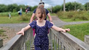 A girl shouts with excitement as she crosses a wobbly bridge.