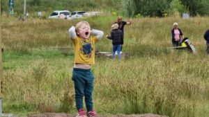 A boy shouts from the top of a grassy knoll near a car park.