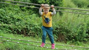 A boy climbs a two-rope crossing, balancing on the bottom rope while holding the top rope.