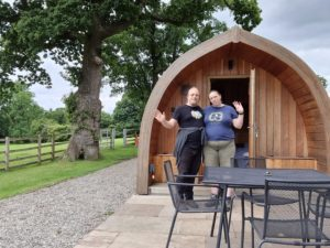 """Dan and Ruth outside a wooden """"pod"""" glamping structure."""