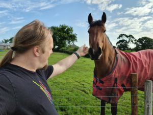 Dan strokes a large brown horse wearing a red jacket.