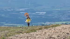 Steve Taylor wearing a bathtub and climbing Pendle Hill.