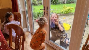 Children in pyjamas at a breakfast table greet Robin outside the patio doors.