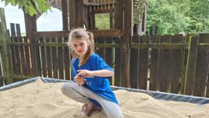 A girl digs in a tabletop sandpit.