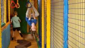 A girl hangs upside-down in a soft play area.