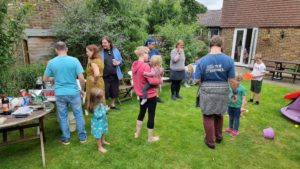 People stand around in a garden at a barbecue.