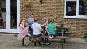 Children at a picnic table in a garden.