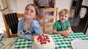 The kids pose with a fruit-topped cake.