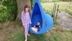 The kids play switch while they hang in a 'nest swing'.