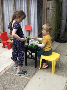 Children play shop: a boy operates a checkout and a girl buys shopping.