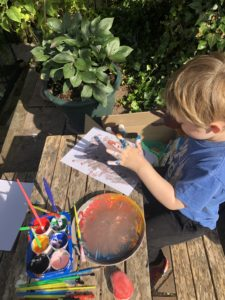 A boy doing finger painting.