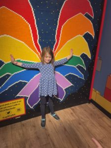 Girl in front of a LEGO mosaic of butterfly wings.