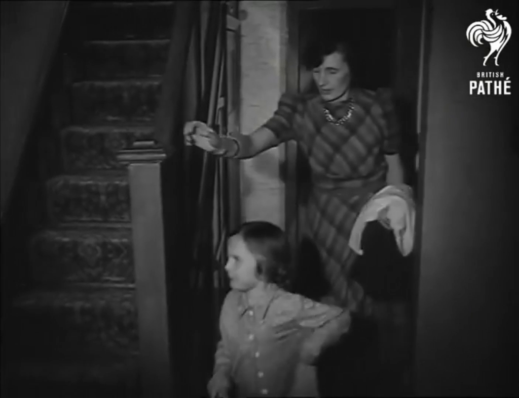Black & white framegrab showing a woman following her child, wearing pyjamas, towards a staircase up.