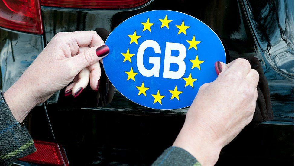 GB sticker being affixed to a car.